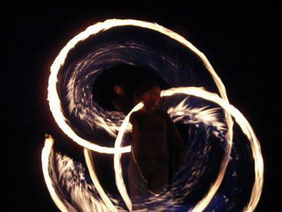 Jongleur entouré de cercles lumineux tracés par ses bolas de feu