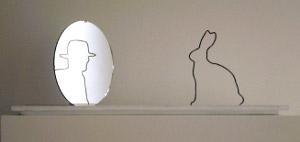 Le reflet d'un lapin sur un miroir représente un homme avec un chapeau