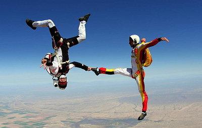 Un parachutiste, position debout, et l'autre parachutiste, position tête en bas, se tiennent par le pied et la main