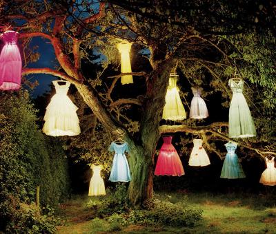 Robes lumineuses accrochées aux branches d'un arbre