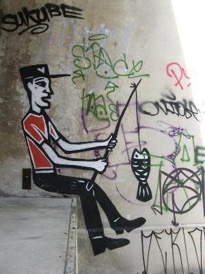 Graffiti d'un poisson suspendu à la ligne d'un pêcheur