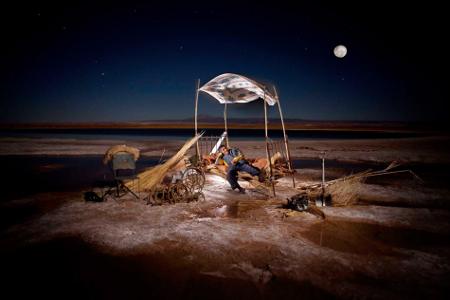Sur une étendue de sable illuminée par la lune, une cabane faite de toile et des bois hétéroclites