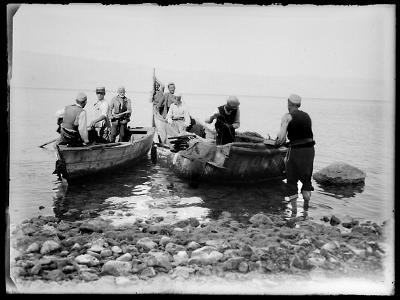 Deux barques et leurs pêcheurs sur une rive d'une grande étendue d'eau