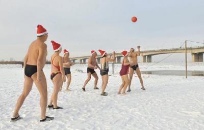 Joueurs en maillot et bonnet jouant au volley sur la neige